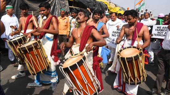A group of demonstrators from Kerala play a traditional drum at the Ghazipur border protest site as the agitation against new farm laws continues in New Delhi on Sunday. (Raj K Raj/HT Photo)
