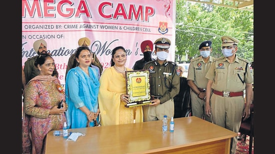 Police commissioner Rakesh Agrawal honouring Punjab State Women Commission Chairperson Manisha Gulati during a camp organised by Ludhiana Police for disposal of complaints related tomatrimonial disputes at Police Lines in Ludhiana on Monday. (Gurpreet Singh/HT)