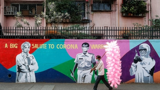 A cotton candy seller walks past a graffiti honouring the frontline workers in fight against Covid-19, on a street in Navi Mumbai on Monday.(Reuters Photo)