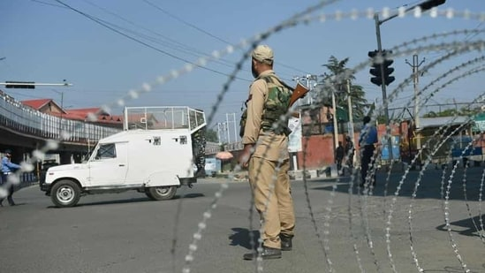 File photo of security personnel on guard on a street during restrictions imposed in the wake of the first anniversary of Article 370 abrogation in Srinagar, August. 5, 2020.(PTI file photo)