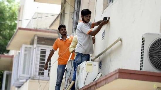 Workers install CCTV cameras at government flats, at Pandara Road, in New Delhi.(Arvind Yadav / Hindustan Times)