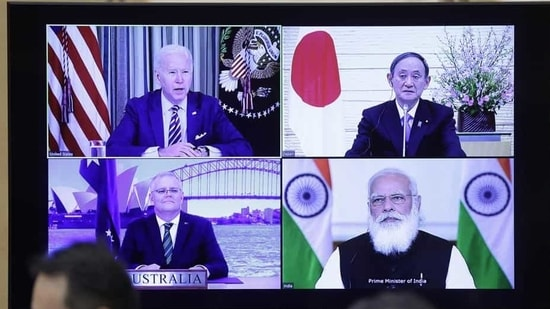 US President Joe Biden, top left, Yoshihide Suga, Japan's prime minister, top right, Scott Morrison, Australia's prime minister, bottom left, and Narendra Modi, India's prime minister, on a monitor during the virtual Quadrilateral Security Dialogue (Quad) meeting at Suga's official residence in Tokyo, Japan.(Bloomberg)