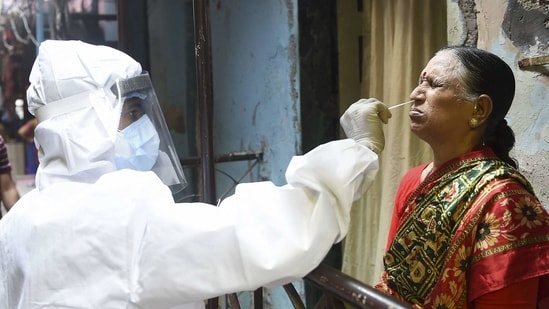 A health worker collects a swab sample from an elderly woman for the Covid-19 test.(Kunal Patil/PTI)