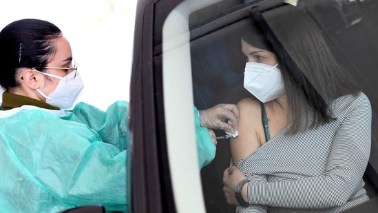 A woman receives the AstraZeneca vaccination against the coronavirus disease (Covid-19) at a drive-through site, in Milan, Italy.(REUTERS)