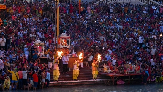 Hindu devotees attend evening prayers after taking a holy dip in the waters of the River Ganges on the Shahi Snan (grand bath) on the occasion of the Maha Shivratri festival during the ongoing religious Kumbh Mela festival in Haridwar on March 11, 2021.(AFP)