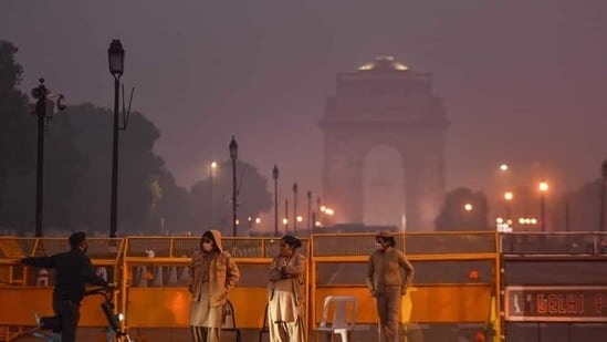 A person using an electric scooter inquires from police personnel manning barricades on Rajpath near India Gate in New Delhi on Saturday, December 12, 2020.(Sanchit Khanna/HT PHOTO)