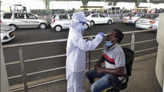A healthcare worker collects swab sample of a passenger at Chhatrapati Shivaji Maharaj International Airport. (HT FILE)