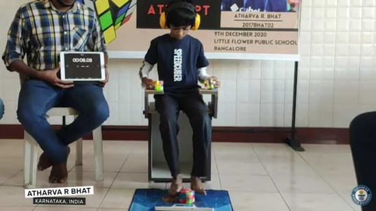 Atharva R Bhat using his hands and feet to solve three cubes.(YouTube/Guinness World Records)