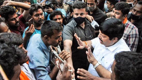 BJP Lok Sabha MP Arjun Singh (R) talks with party workers protesting against party's National Vice President Mukul Roy over selection of candidates for the upcoming West Bengal assembly polls, outside BJP election office in Kolkata. (PTI Photo)
