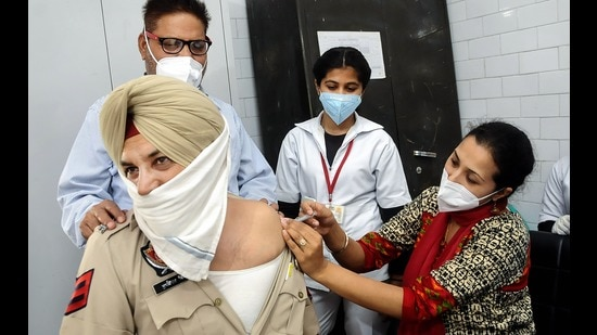 A medic administers the Covid-19 vaccine to a Punjab Police officer during a countrywide inoculation drive in Patiala Wednesday (PTI)