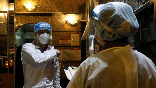 Workers wearing protective suits arrive at the locked-down part of the Sai Ying Pun area to contain a new outbreak of coronavirus disease (Covid-19) in Hong Kong, China.(Reuters file photo)