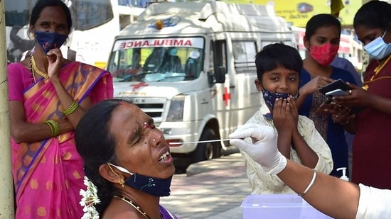 A health worker conducts COVID-19 testing of a passenger at KSRTC bus stand, amid surge in coronavirus cases in Bengaluru. (PTI Photo)