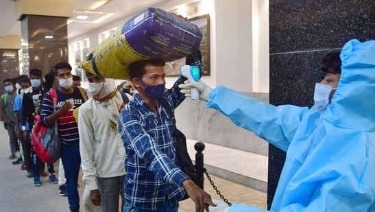 Maharashtra, which is the worst hit as a second wave of infections starts in India, ordered all theatres and auditoriums to operate at 50% capacity, and allow no one to enter without masks. In this file picture, a frontline worker checks temperature of people in Mumbai. (PTI)