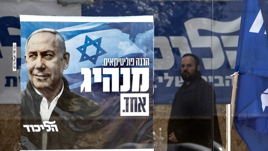 A man walks past a Likud party campaign poster for Prime Minister Benjamin Netanyahu in the city of Sderot, Israel.(AP)