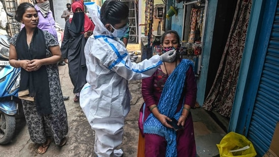 A health worker collects a nasal swab sample from a woman at a residential area in Mumbai.(AFP)