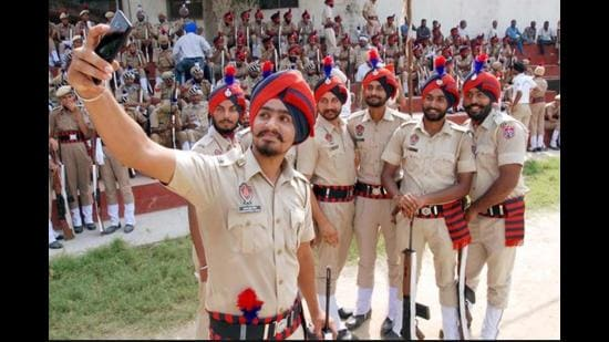 Punjab Police personnel taking a selfie after a marchpast in Amritsar. Apart from 3,100 domain experts to combat specialised crimes, 10,000 police officials will be recruited, of which 33% will be women, at the level of sub inspector and constables. (Sameer Sehgal/HT file photo)