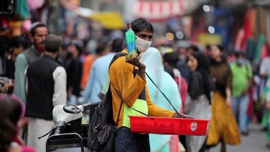 An Indian vendor wearing face mask as a precaution against the coronavirus sells curios at Sunday market in Jammu, India.(AP)