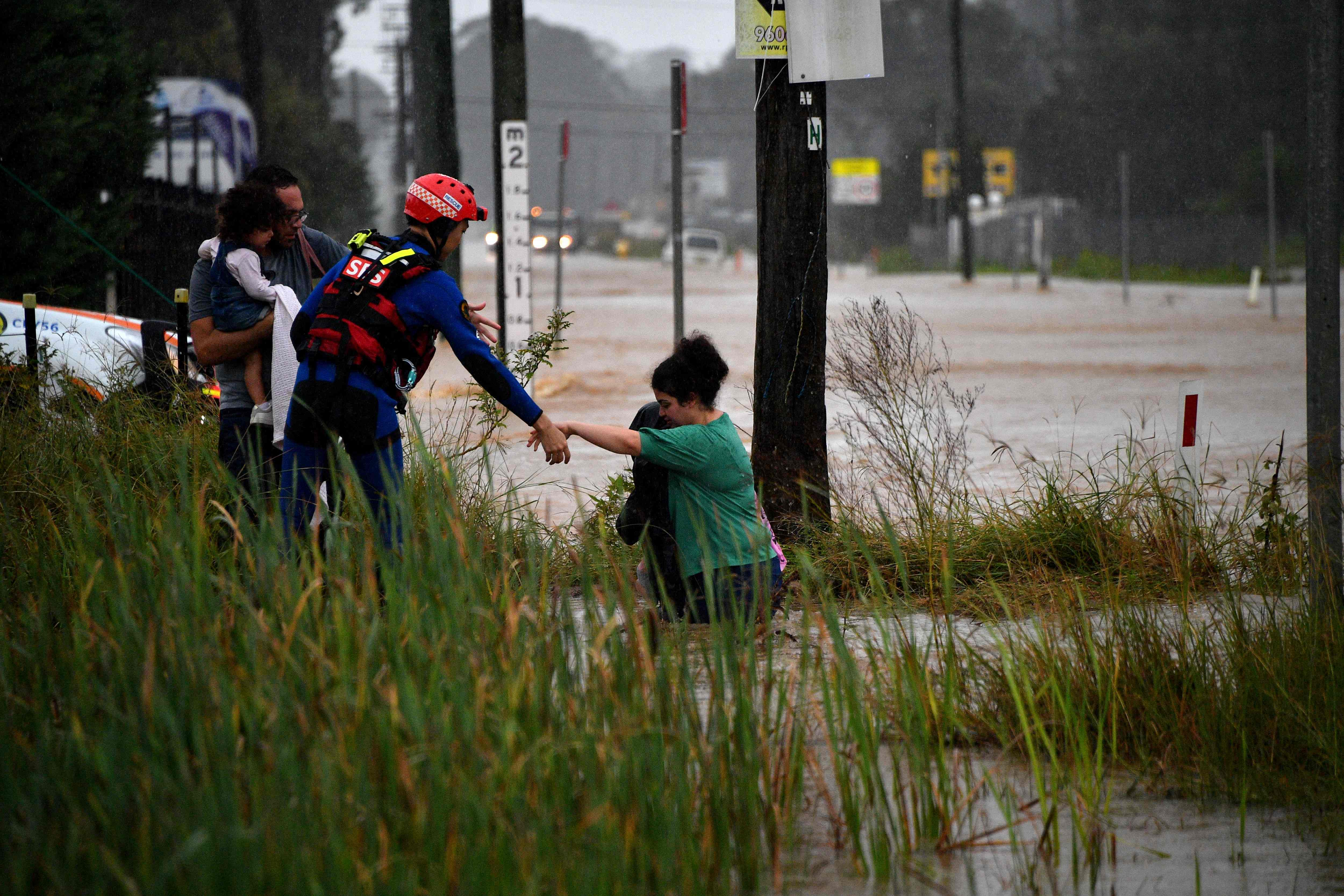 A rescue worker helps residents cross a flooded road during heavy rain in western Sydney.(AFP)