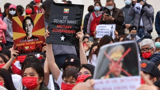 People hold placards as they gather to denounce the Myanmar military coup.(REUTERS)