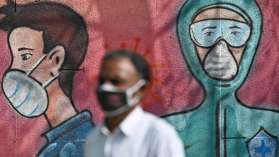 A pedestrian walks past a wall mural depicting frontline coronavirus warriors wearing face masks along a road.(AFP)