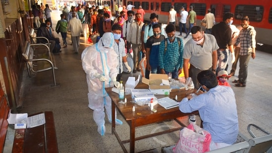 Passengers wait in a queue to give samples for their Covid-19 tests after arriving at a railway station, in Mirzapur.(PTI)
