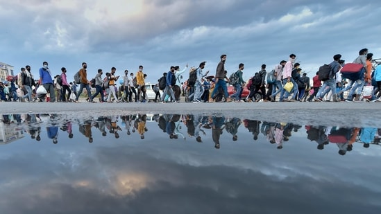 A group of migrant workers walk to their native places amid the nationwide complete lockdown, on the NH24 near Delhi-UP border in New Delhi, Friday, March 27, 2020. (PTI)
