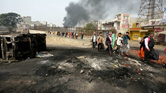 Members of a wedding procession are seen walking on a road littered with debris and damaged vehicles, while smoke rises in the background at Karawal Nagar.(Biplov Bhuyan/ HT Archive)