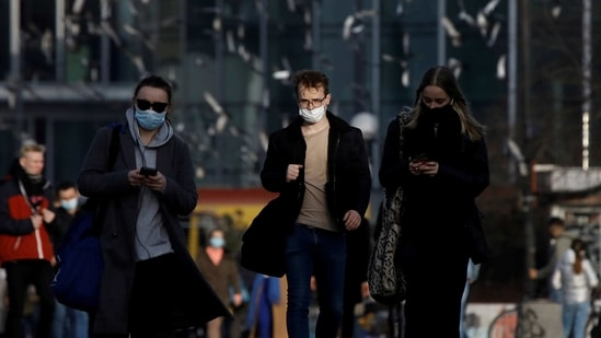 People wearing protective masks amid the outbreak of coronavirus disease (Covid-19) walk in the centre of Warsaw, Poland. (REUTERS)