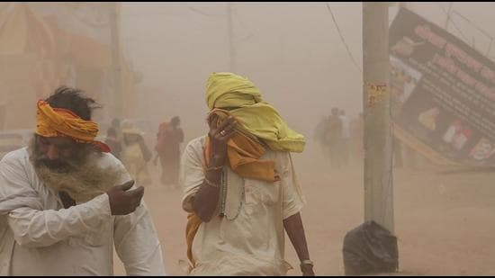 People cover their faces against a dust storm, at Vrindavan in Mathura district, Uttar Pradesh, on Tuesday, March 23. (PTI)