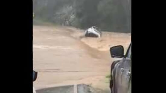 The image shows the car being swept away.(Twitter/@TMRQld)