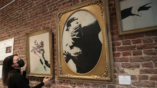 """An art handler shows to reporters work """"Love Is In The Air"""" by street artist Banksy, as preparations take place for the exhibition """"Banksy, The Brussels Show"""", that will present the artist's most representative works, in Brussels, Belgium March 24, 2021. (REUTERS)"""