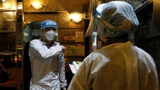 Workers wearing protective suits arrive at the locked-down part of the Sai Ying Pun area to contain a new outbreak of coronavirus disease (Covid-19) in Hong Kong, China.(Reuters)