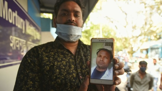 A relative showing a picture of Lokesh who died inside a manhole while cleaning the septic tank at Grand Emperor Banquet Hall, in Ghazipur, New Delhi, India, on Friday, March 26, 2021. Two people dies in the incident. (Photo by Amal KS / Hindustan Times)
