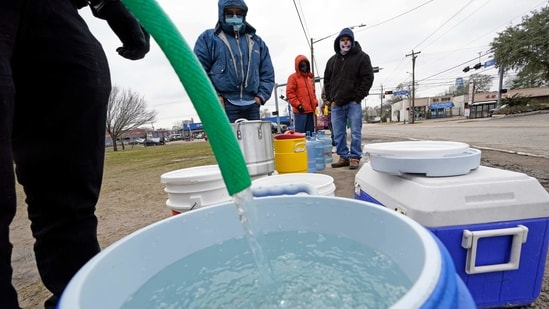 A water bucket is filled as others waited in near freezing temperatures to use a hose from public park spigot in Houston on February 18, 2021. (AP File Photo )