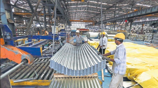 Employees guide finished corrugated steel roofing onto a pallet in the tube mill at the manufacturing facility of Uttam Galva Steels Ltd., the Indian unit of ArcelorMittal, in Khopoli, Maharashtra, India, on Friday, June 13, 2014. ArcelorMittal, the world's largest steelmaker and one of the few foreign steel mills with investments in China, welcomed the potential removal of a near 10-year block on overseas takeovers in China's steel industry. Photographer: Vivek Prakash/Bloomberg (Bloomberg)