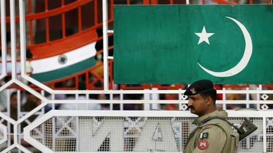 A Pakistani Ranger stands near the Pakistani flag and Indian flag (L) during a daily parade at the Pakistan-India joint check post at Wagah border, February 26, 2010(REUTERS)