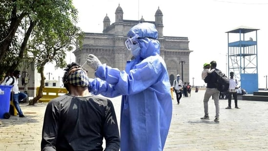 A BMC health worker collects a swab sample to test for Covid-19 infection, at Gateway of India. (Anshuman Poyrekar/HT Photo)