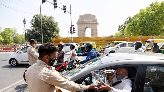 Civil Defence personnel distribute Covid-19 awareness kit to people ahead of the Holi festival, at India Gate in New Delhi. (ANI Photo)