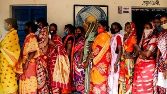 Voters stand in a queue to cast their votes during the first phase of elections in West Bengal in Pirakata, India.