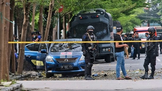 Police officers inspect the area outside the church where an explosion went off in Makassar, South Sulawesi, Indonesia.(AP)