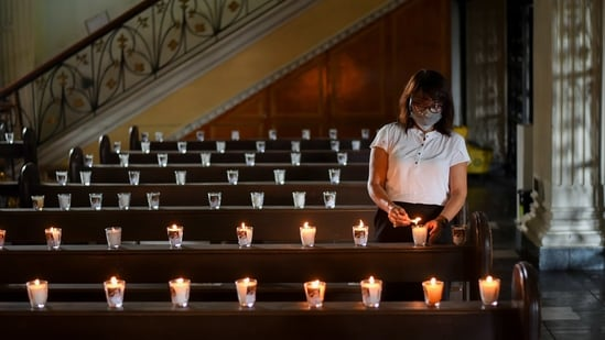 A woman wearing a face mask and a face shield as protection against the coronavirus disease (Covid-19) lights candles before a Palm Sunday mass at the St. Peter Parish Church in Quezon City, Metro Manila, Philippines.(Reuters)