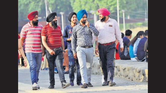 Visitors enjoying a stroll at Sukhna Lake, Chandigarh, on a hot Sunday. Disregard towards Covid-appropriate behaviour, including wearing masks and social distancing, continues at public places across the city despite the rising cases and administration's appeals. (Keshav Singh/HT)