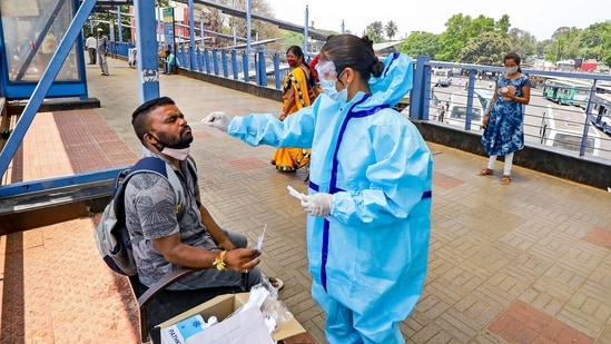 A health worker takes a swab sample from a man for the Covid-19 test, at Kempegowda bus stand in Bengaluru on Friday.(PTI)