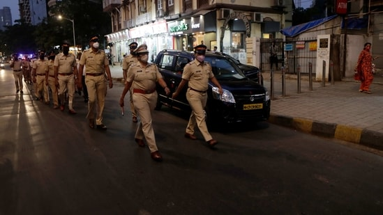Police officials conduct a flag march during the night curfew imposed by the authorities following the rise in COVID-19 cases in Mumbai, India, Sunday, March 28, 2021. (AP)