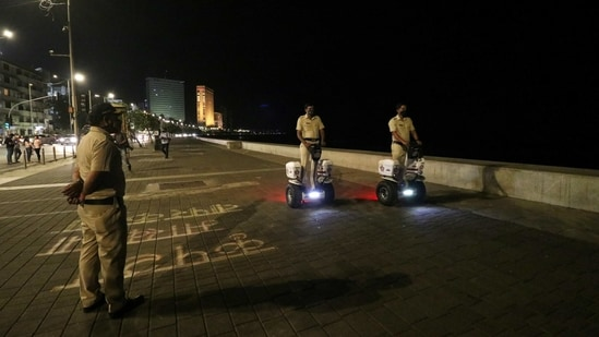 Police officers patrol on Segways along the promenade at Marine Drive during a night curfew in Mumbai on Monday.(Reuters Photo)
