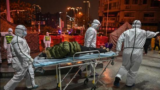 A file photo taken on January 25, 2020 shows medical staff arriving with a patient at the Wuhan Red Cross Hospital in Wuhan, China. (AFP)