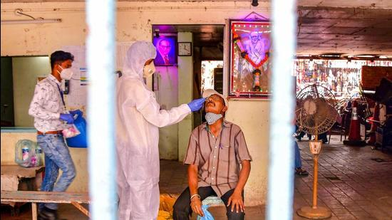A heath worker conducts Covid-19 testing of a man at Dadar market, amid a surge in coronavirus cases across Maharashtra, in Mumbai on March 22. (File photo)