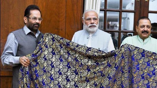 New Delhi: Prime Minister Narendra Modi hands over a Chaadar to be offered at Dargah Khwaja Moinuddin Chishti, Ajmer Sharif to the minority affairs minister Mukhtar Abbas Naqvi (PTI)