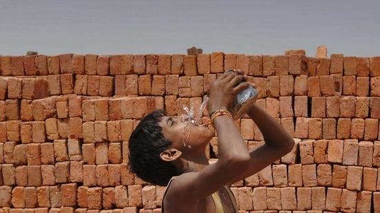 Labourers work at a brick kiln on a hot summer day in Noida.(Burhaan Kinu/HT File Photo)