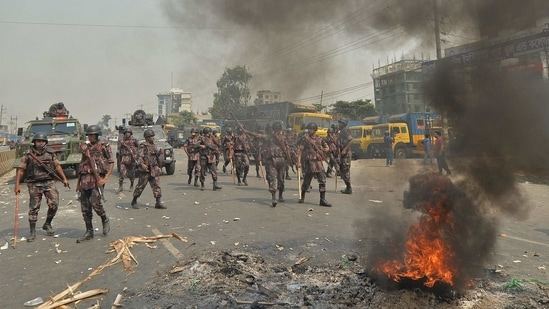 Border Guards Bangladesh personnel stand guard as activists from Hefazat-e Islam block a road during a strike following deadly clashes with police over Prime Minister Narendra Modi's visit, in Narayanganj, about 16 km southeast of Dhaka on March 28(AFP)
